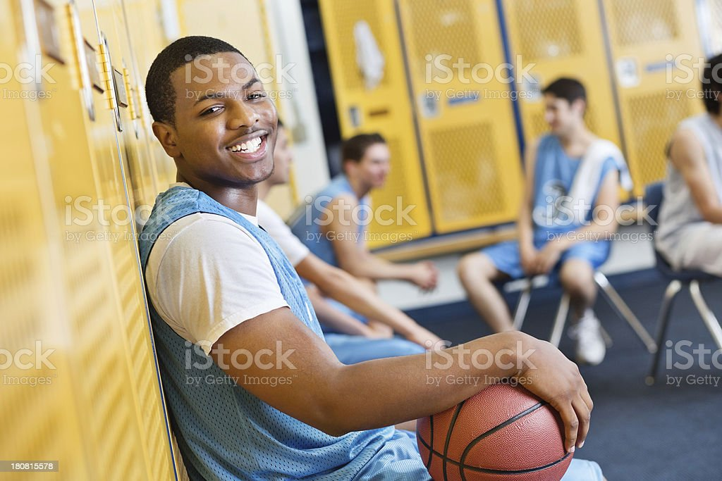 Happy teenage basketball player in high school locker room stock photo