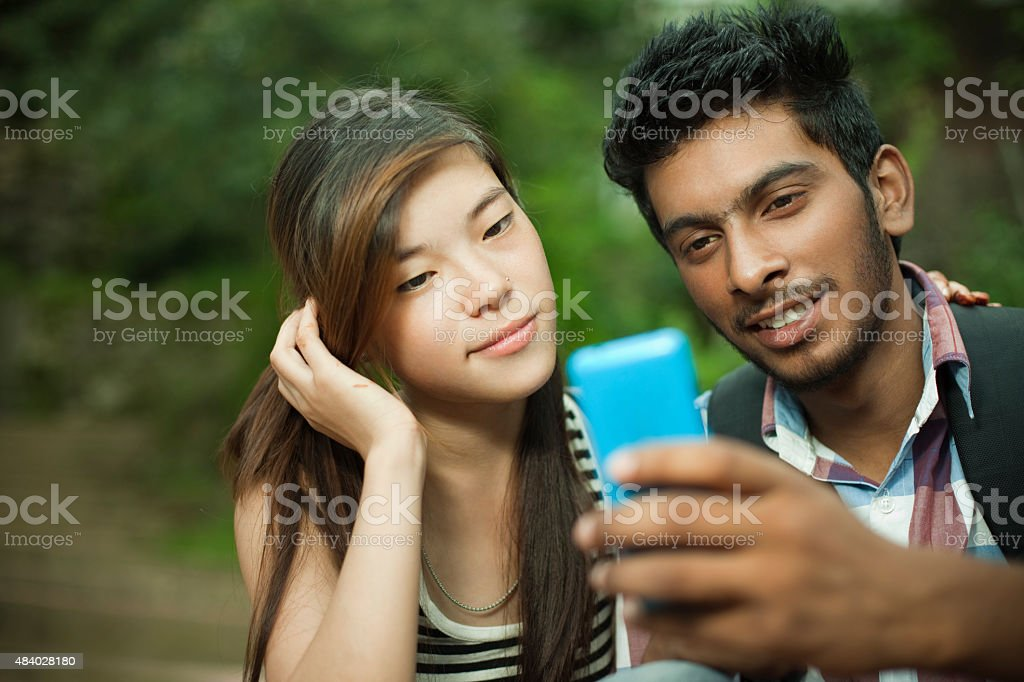 Happy teenage boy and girl of different ethnicity sharing mobilephone. stock photo
