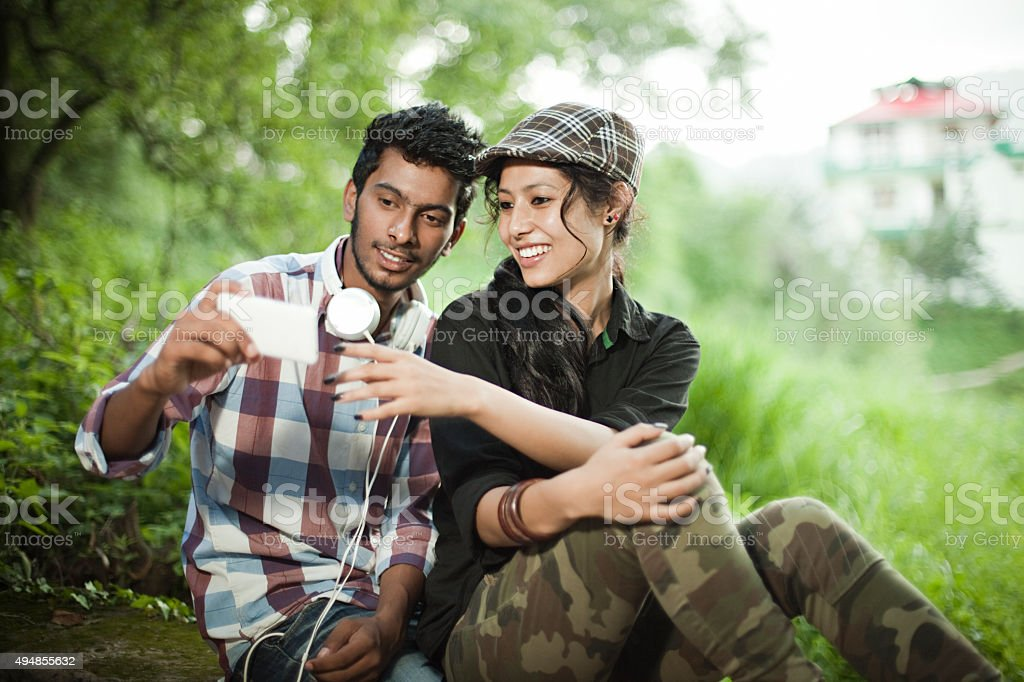 Happy teenage boy and girl of different ethnicity sharing smartphone. stock photo