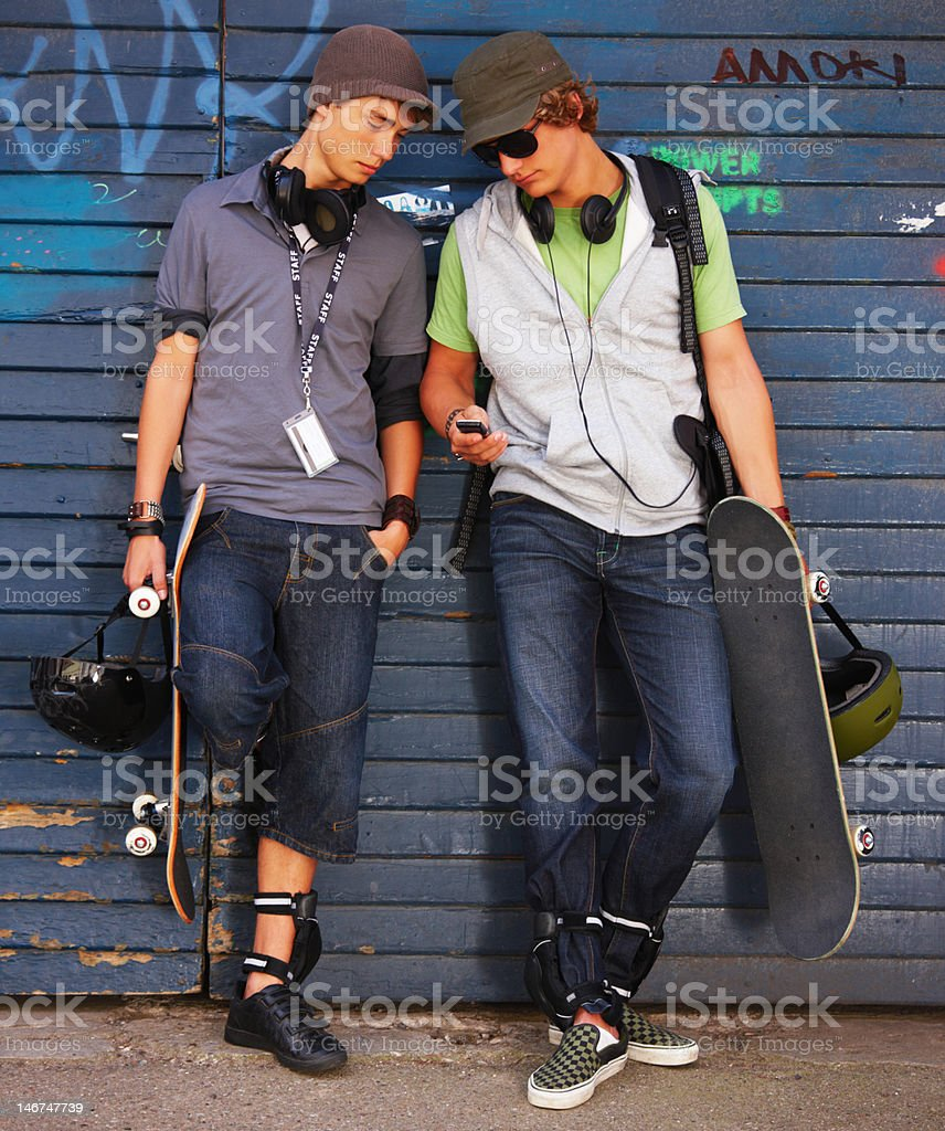 Happy teenage boys looking on cellphone with skateboards and helmet royalty-free stock photo