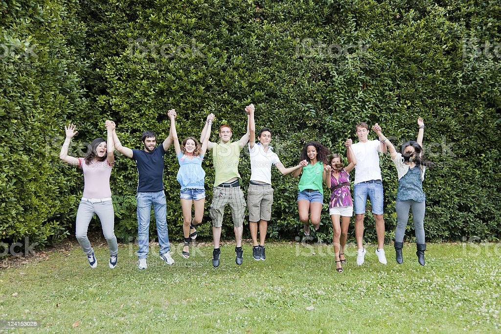 Happy Teenage College Students Jumping at Park royalty-free stock photo