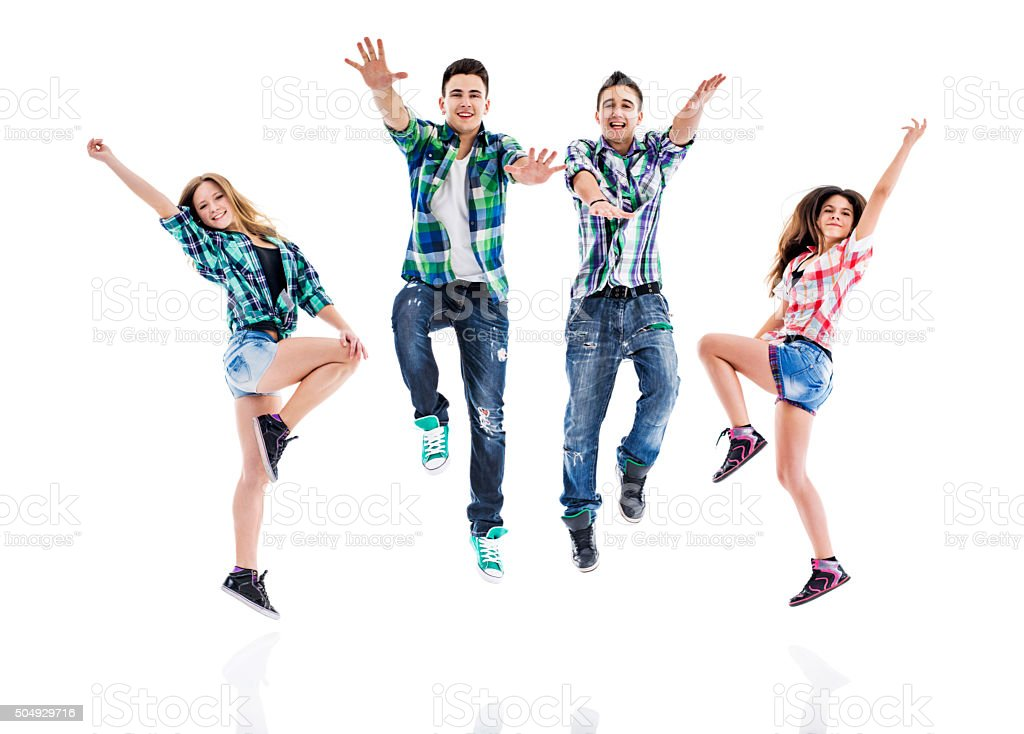 Happy teenage dancers jumping while dancing. stock photo