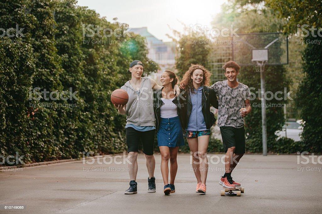 Happy teenage friends enjoying on basketball court stock photo