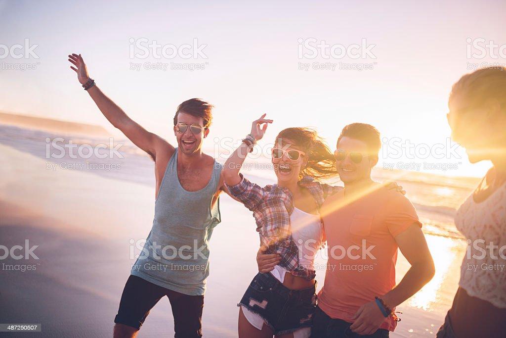 Happy teenage friends on beach stock photo