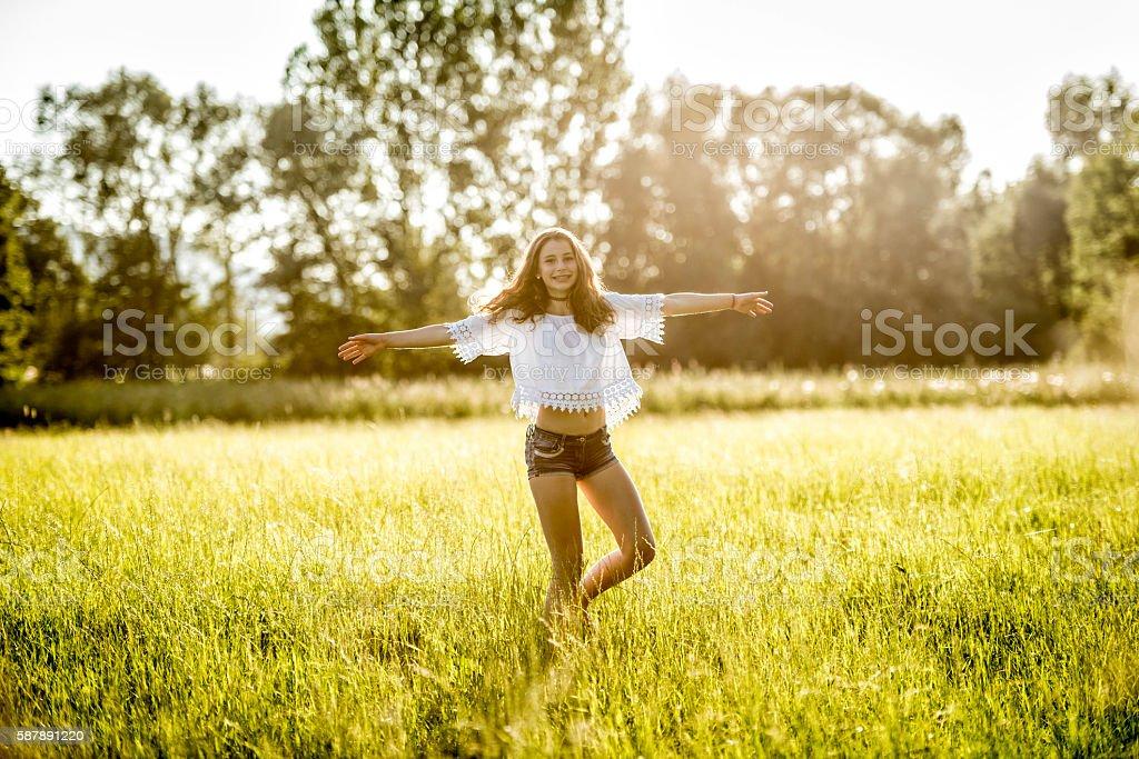 happy teenage girl dancing in meadow stock photo