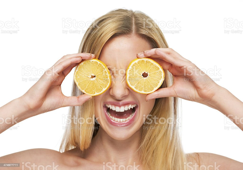 Happy teenage girl holding lemon in front of eyes stock photo
