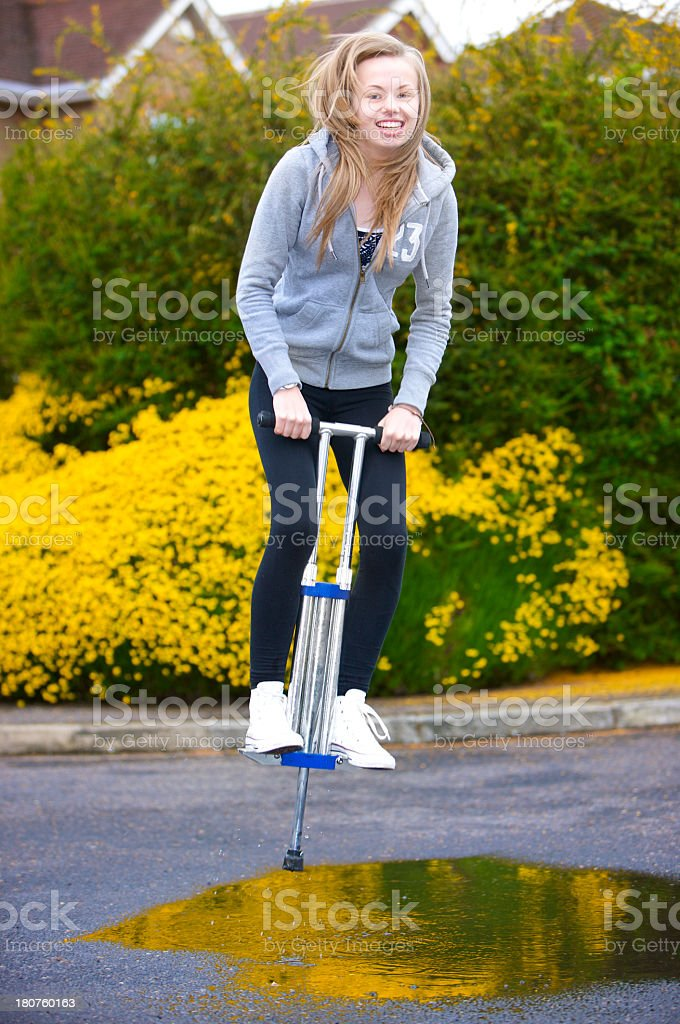 Happy teenage girl jumping through puddle on a Pogo Stick stock photo