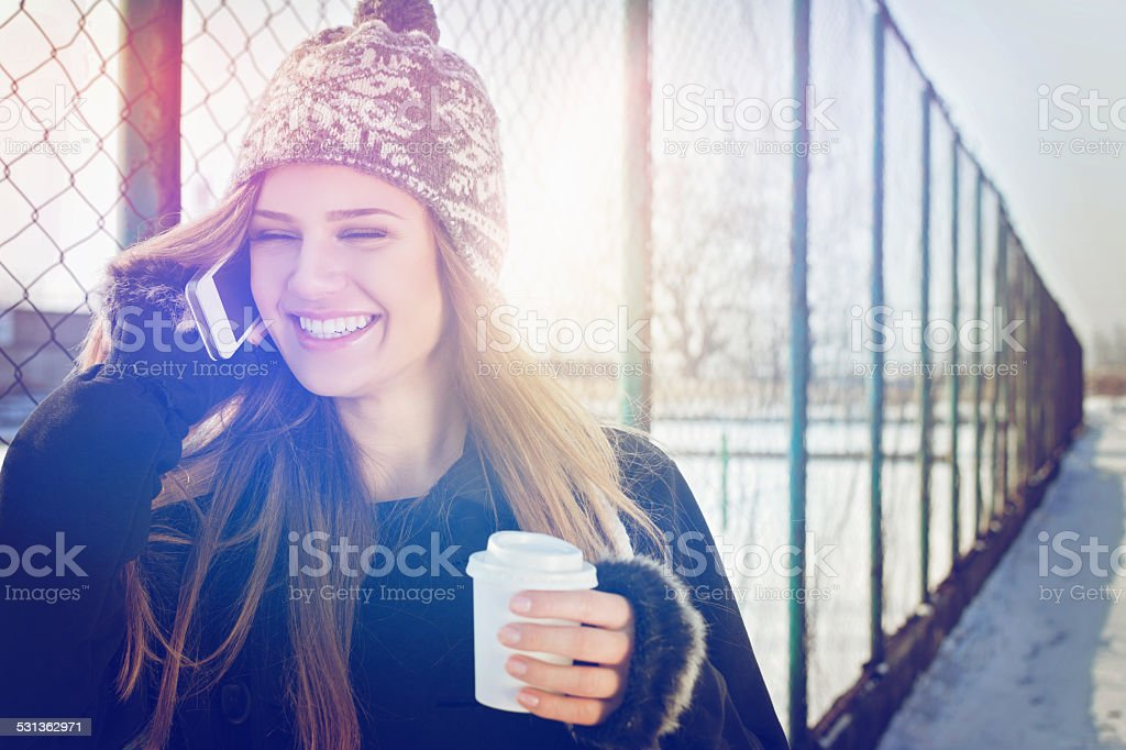 Happy teenage girl with takeaway coffee talking on smartphone stock photo
