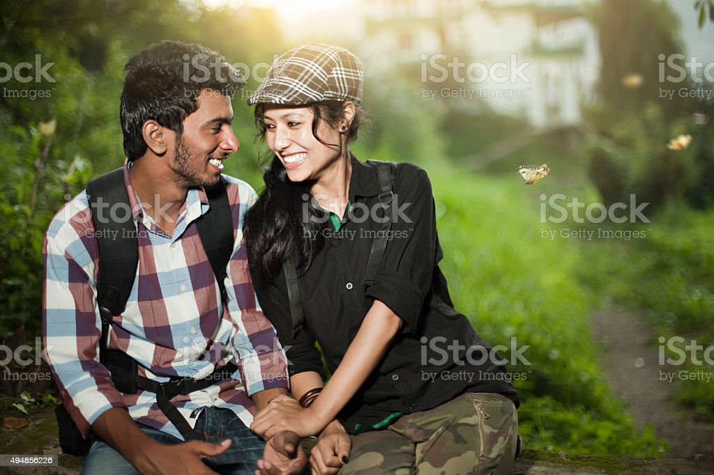Happy teenage lovers of different ethnicity together in tranquil place. stock photo
