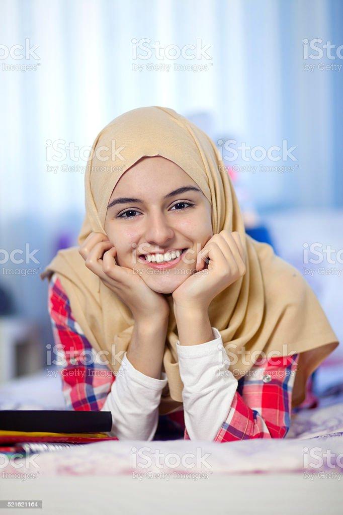 Happy teenage muslim girl lying on bed stock photo