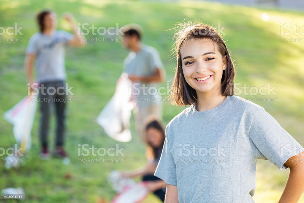 Happy teenager at a park clean up with community volunteers stock photo