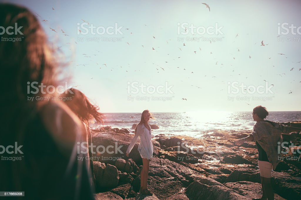 Happy teenager friends enjoys the beach and seagulls stock photo