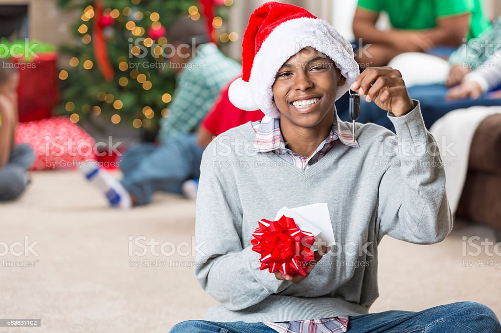 Happy teenager gets keys to a car for Christmas stock photo