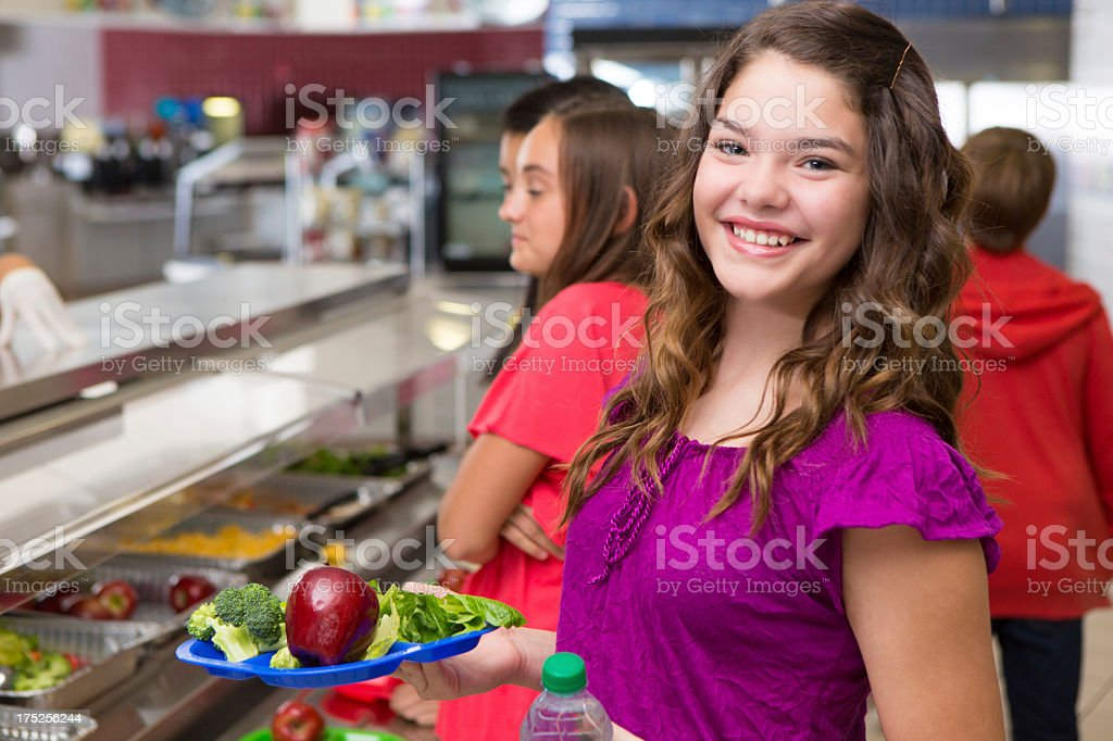 Happy teenager holding her lunch at the school cafeteria stock photo