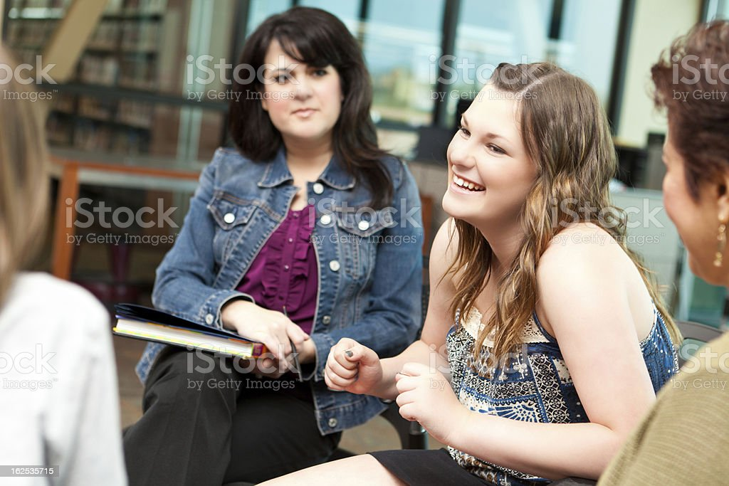 Happy teenager in a group discussion setting stock photo