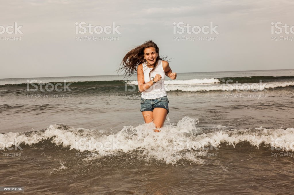 Happy teenager playing with the water at the seashore stock photo