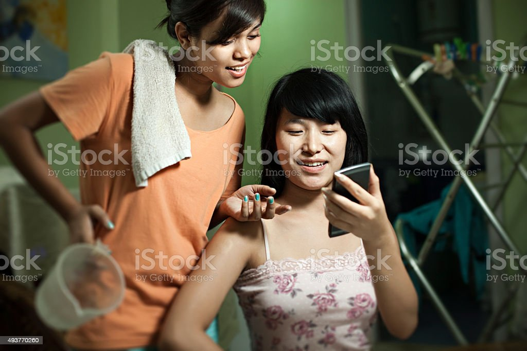 Happy teenager roommate girls from different ethnicity sharing smart phone. stock photo