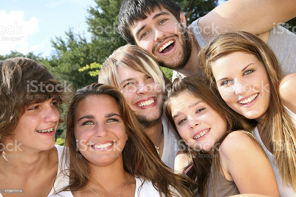 Happy Teenagers Grouping Together To Take A Photo stock photo