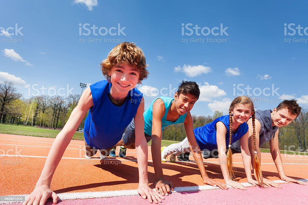 Happy teenagers holding plank outdoor on the track stock photo