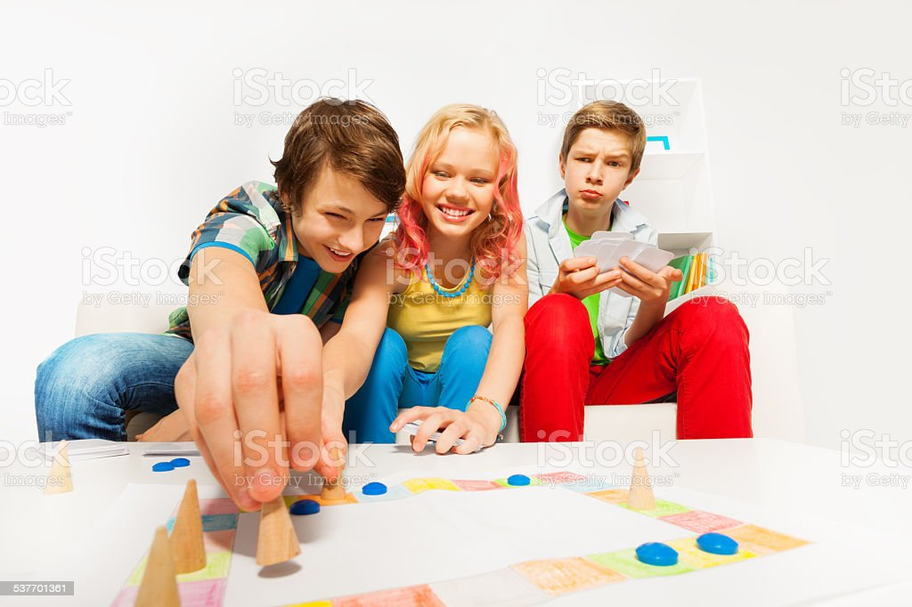 Happy teenagers play table game together at home stock photo