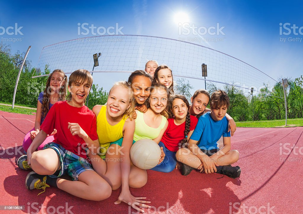 Happy teenagers sitting on volleyball court stock photo
