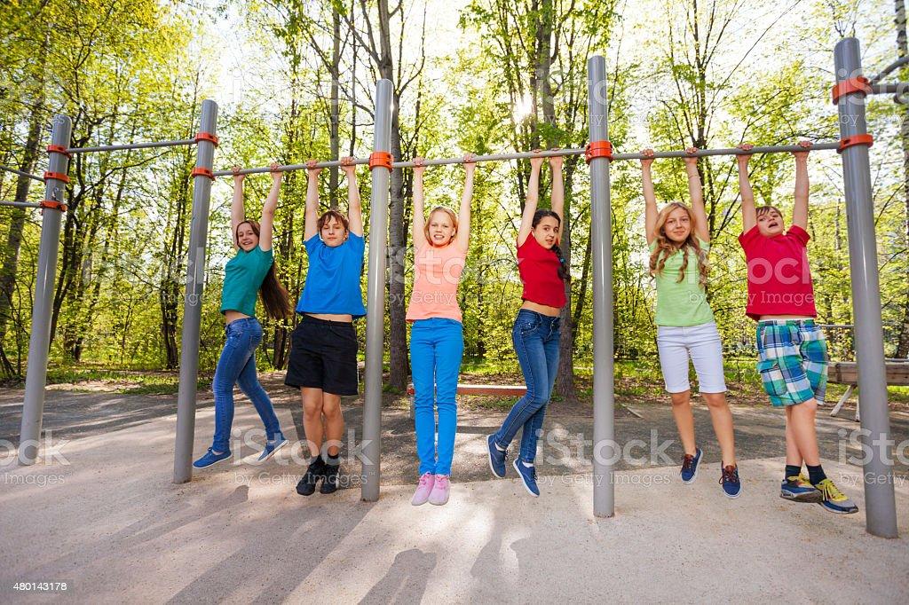 Happy teens chinning up on the playground stock photo