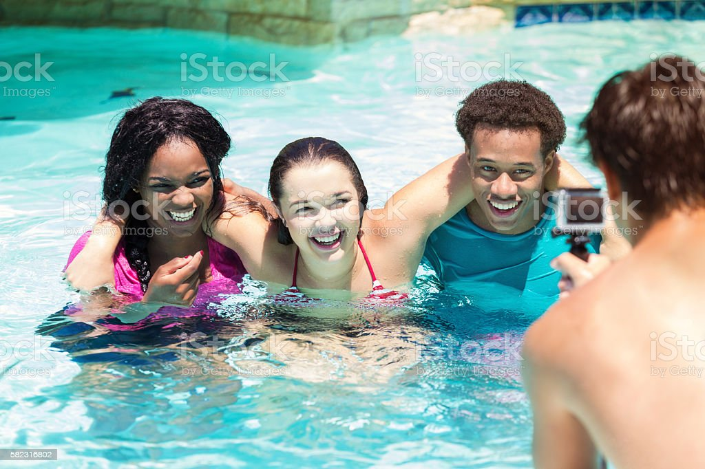 Happy teens laughing together in the pool with wearable camera stock photo