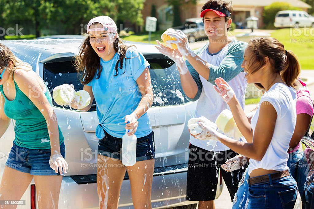 Happy teens playing and splashing around at a car wash stock photo
