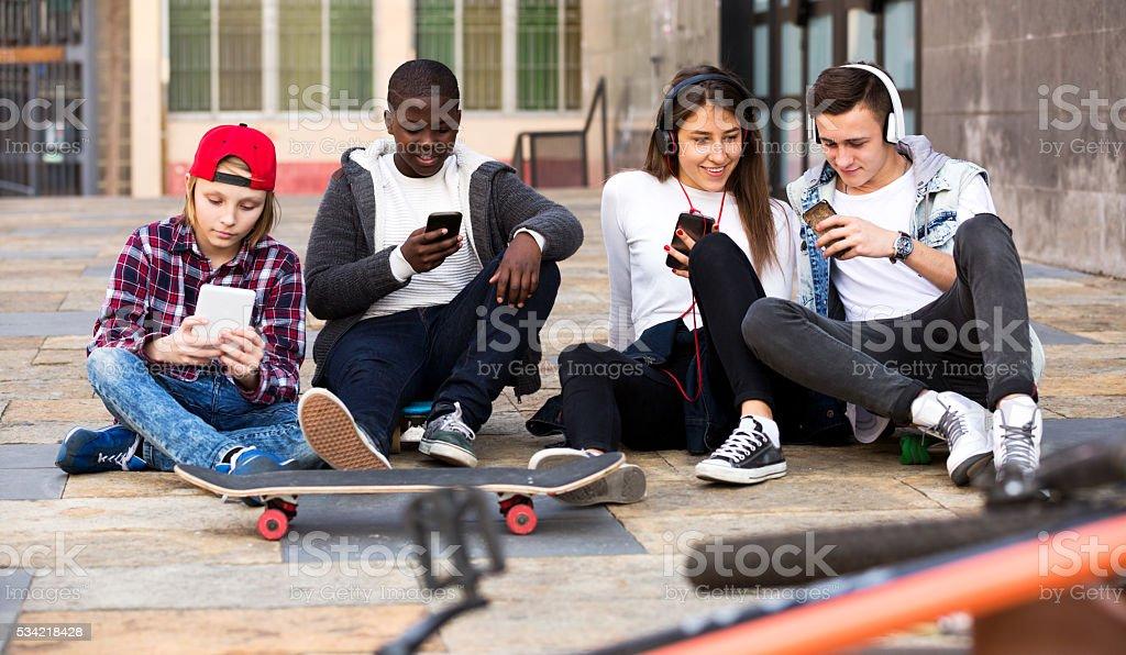 Happy teens playing on smarthphones stock photo