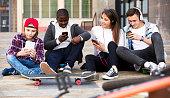 Happy teens playing on smarthphones