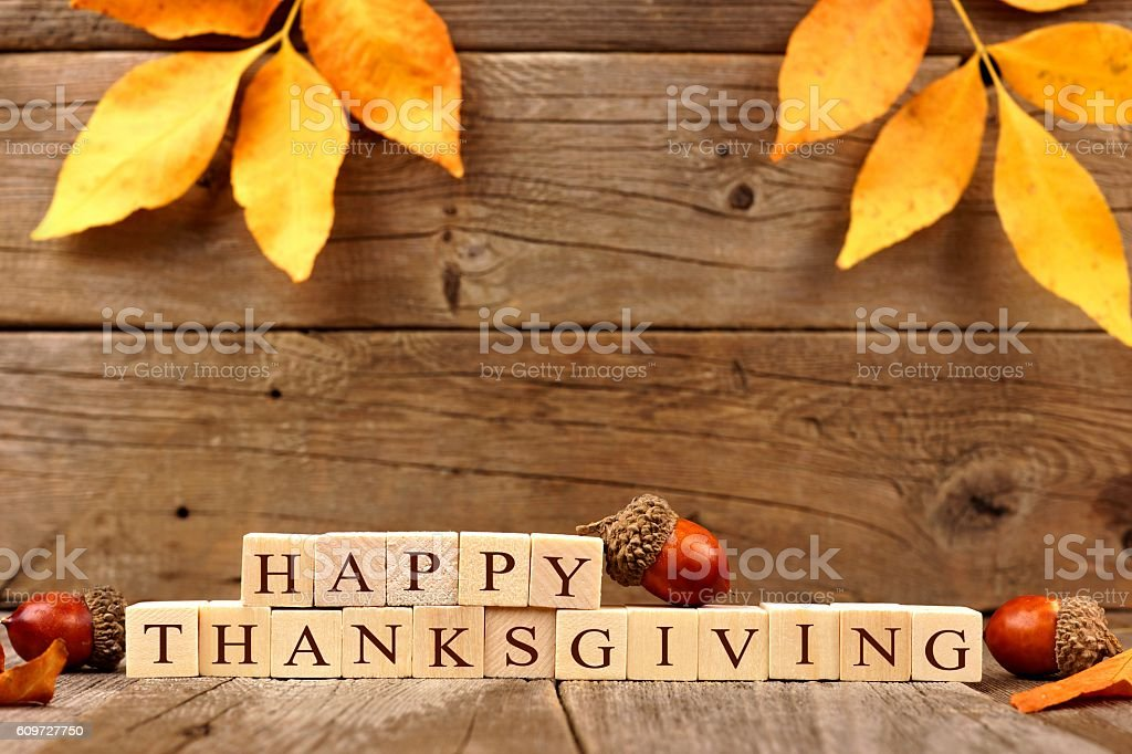 Happy Thanksgiving wooden blocks with wood background, acorns, leaves stock photo