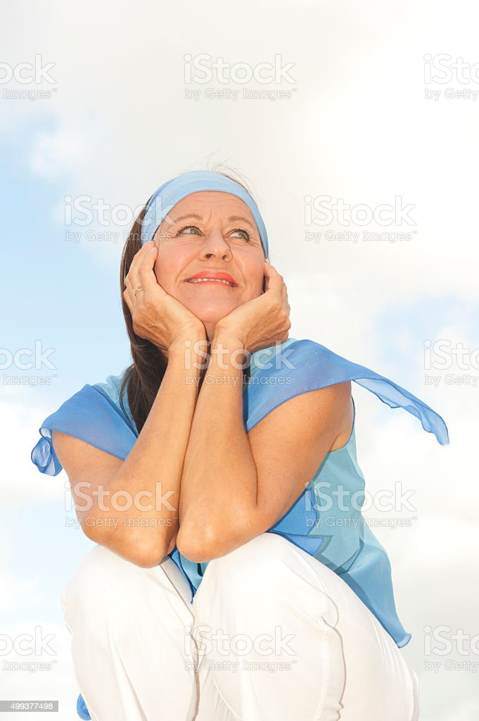 Happy thoughtful middle aged woman outdoor stock photo