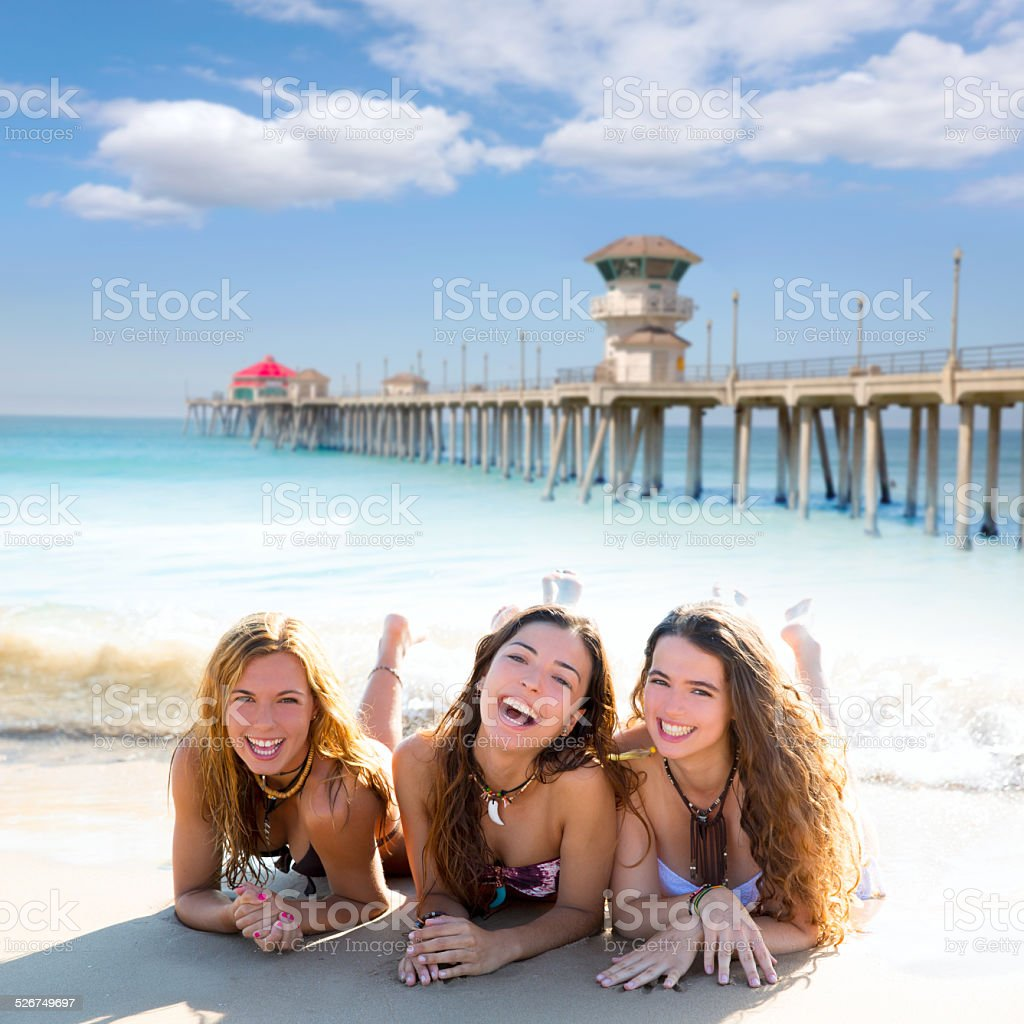 happy three friends girls lying on beach sand smiling stock photo