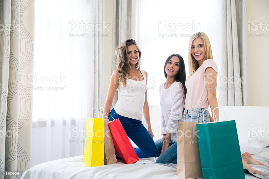 Happy three girlfriends with shopping bags stock photo