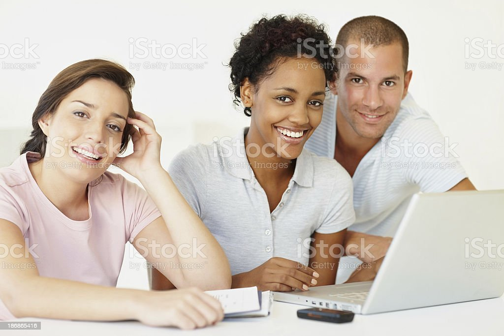 Happy three young students using a computer laptop royalty-free stock photo