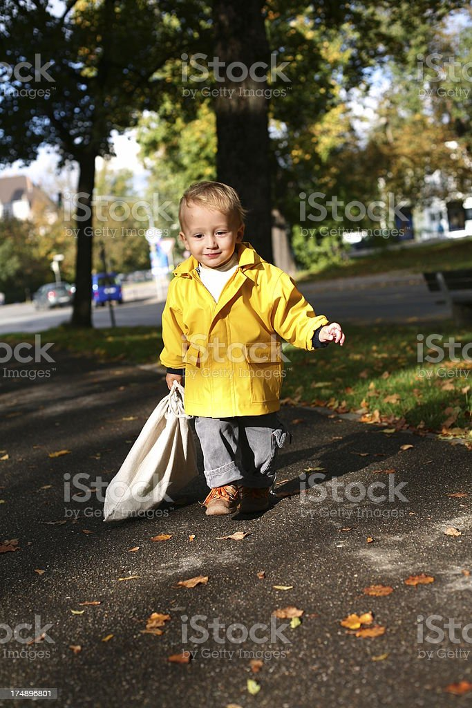 Happy toddler draging a clothbag stock photo