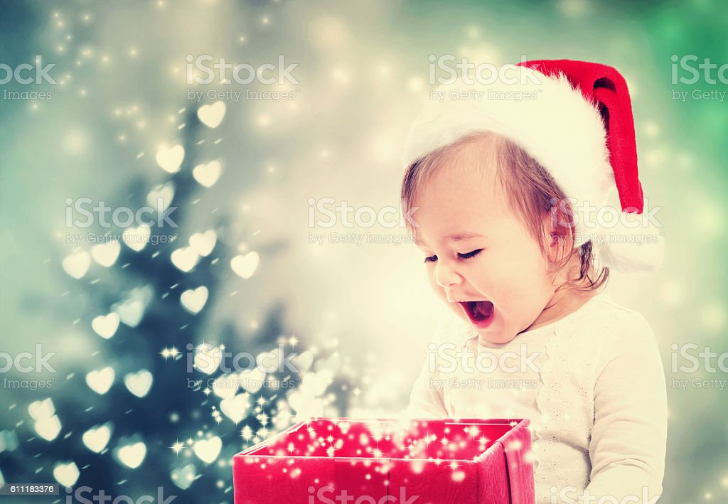 Happy Toddler girl looking at Christmas present box stock photo