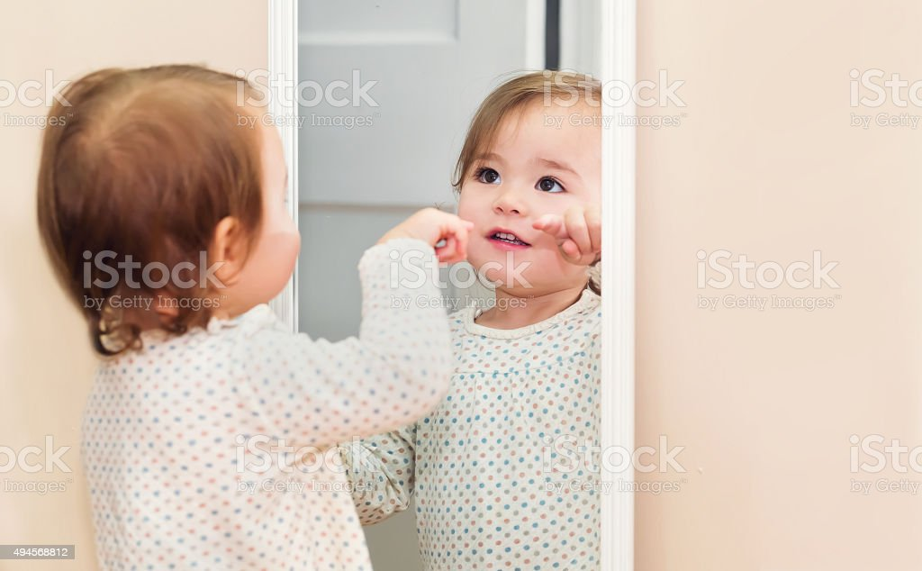 Happy toddler girl looking at herself in the mirror stock photo