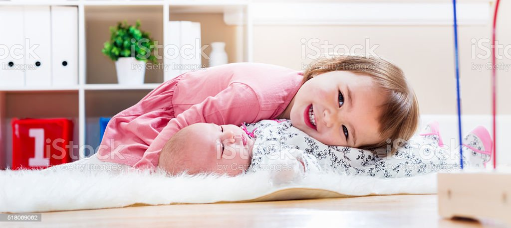 Happy toddler girl playing with her baby sibling stock photo