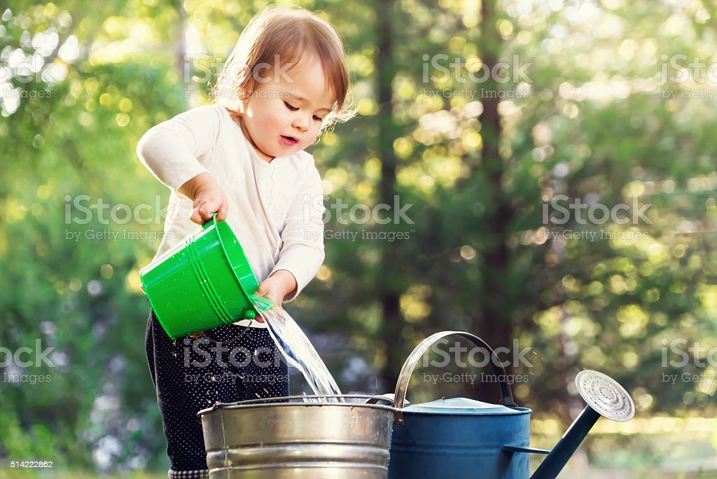Happy toddler girl playing with watering cans stock photo