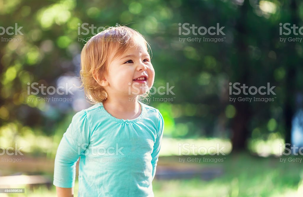 Happy toddler girl smiling outside stock photo