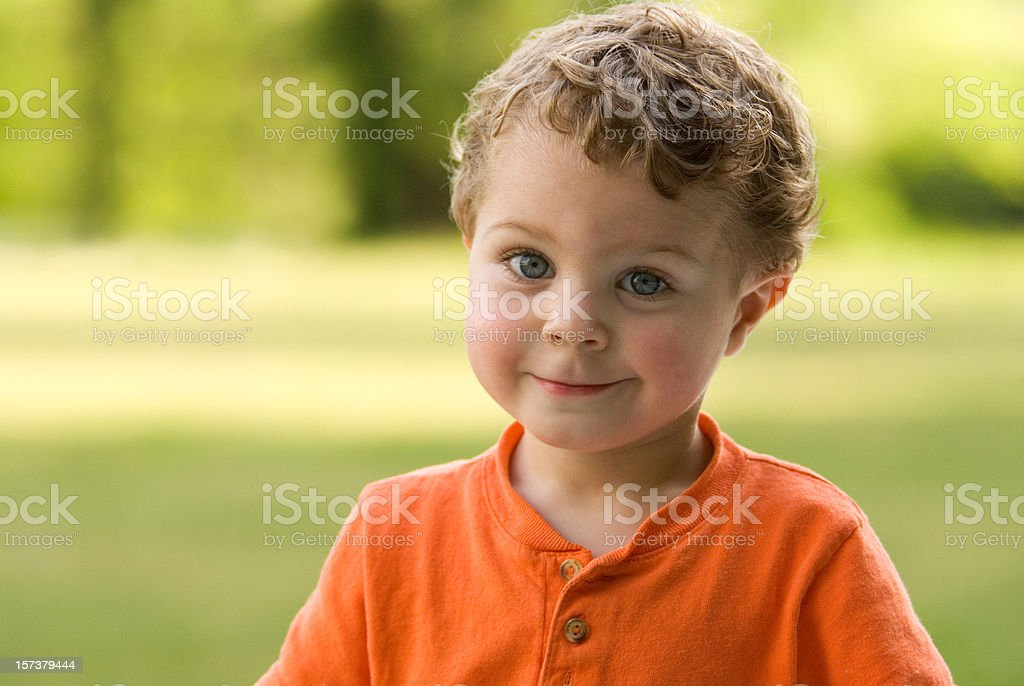 Happy Toddler (Boy) In Front of A Grass Field royalty-free stock photo