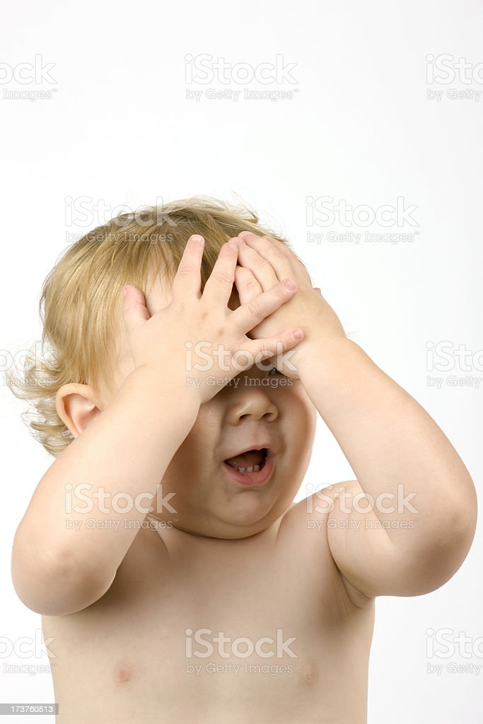 Happy Toddler Playing Hide Seek by Covering His Face royalty-free stock photo