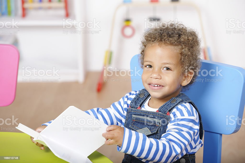 Happy Toddler Reading to Himself In A Nursery Setting royalty-free stock photo