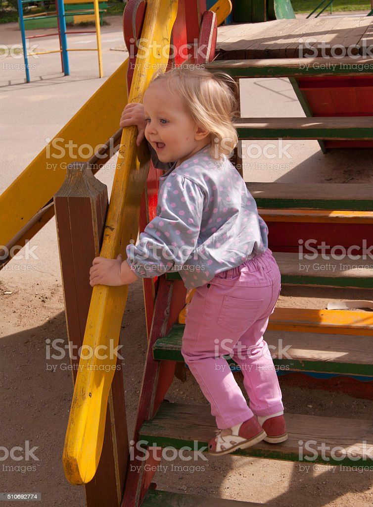 Happy toddler shouting on the wooden slide steps stock photo