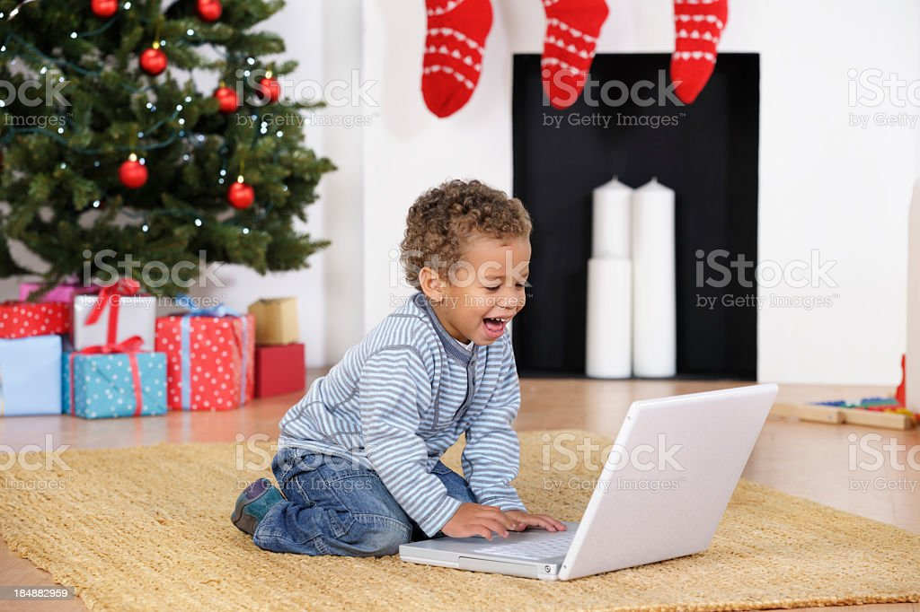 Happy Toddler Using A Laptop At Christmas stock photo