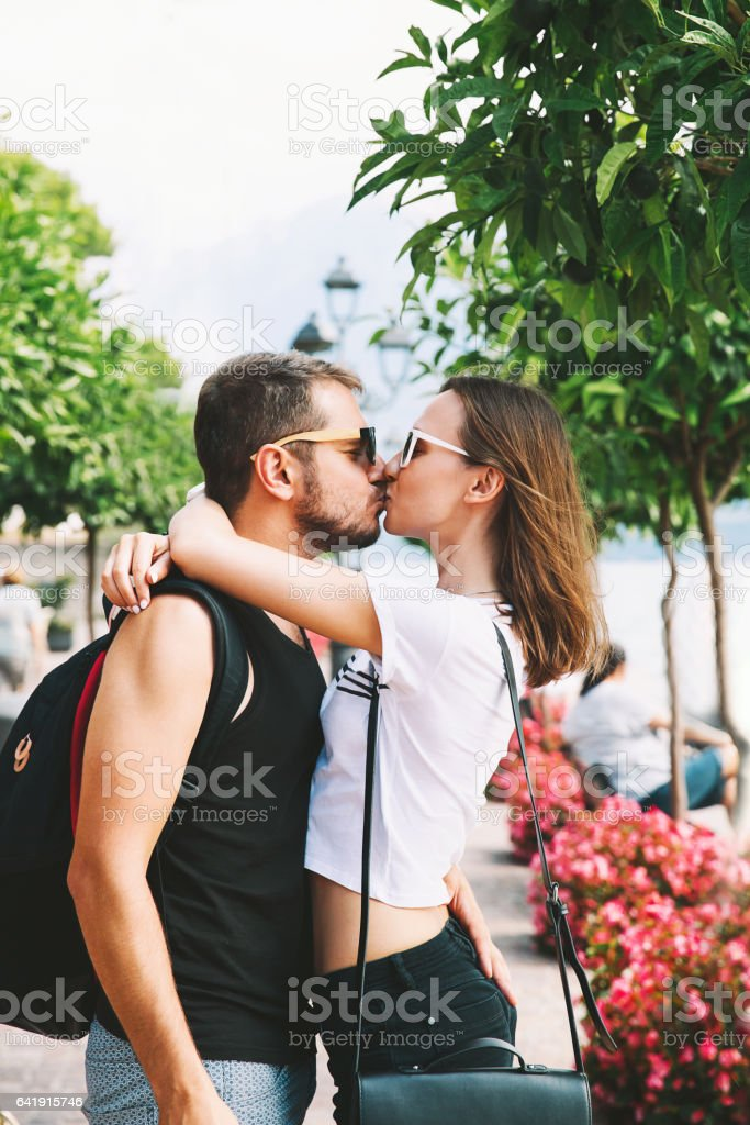 Happy tourist, young couple of lovers kissing at Lake Garda, Italy, Europe. stock photo