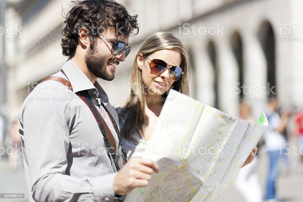 Happy tourists couple holding map stock photo