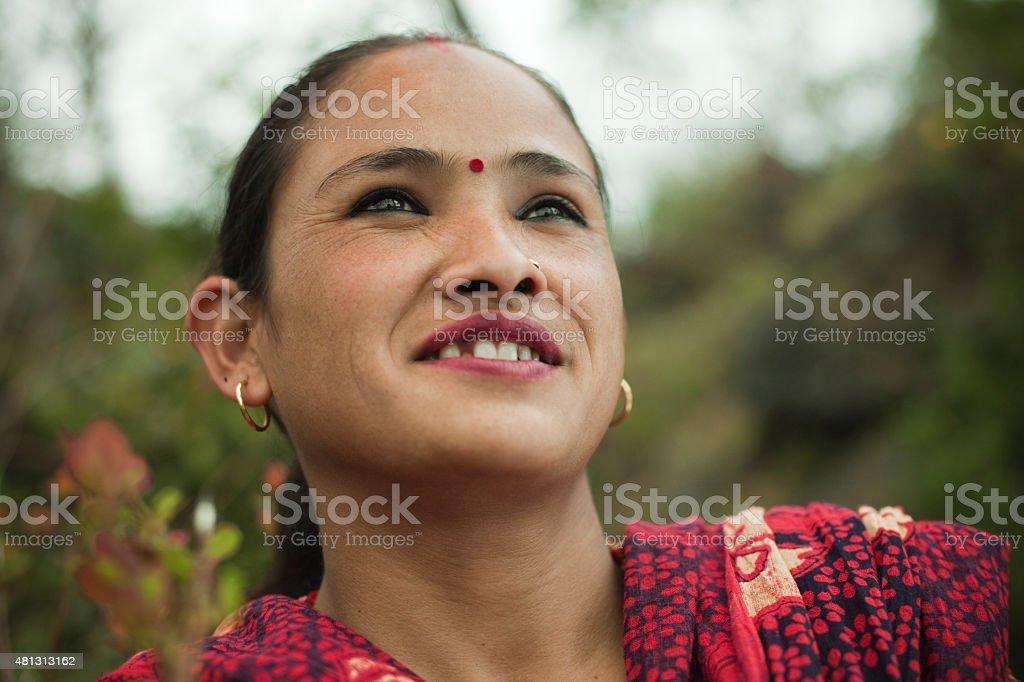 Happy traditional Asian woman in rural nature looking away upward. stock photo