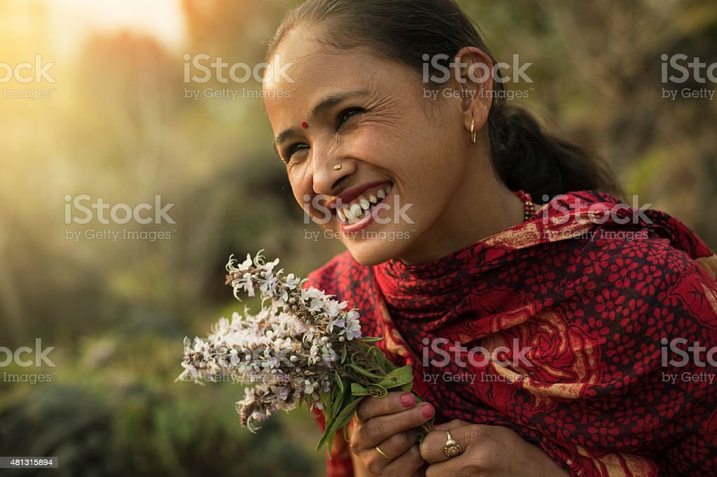 Happy traditional Asian woman looking away in rural nature. stock photo